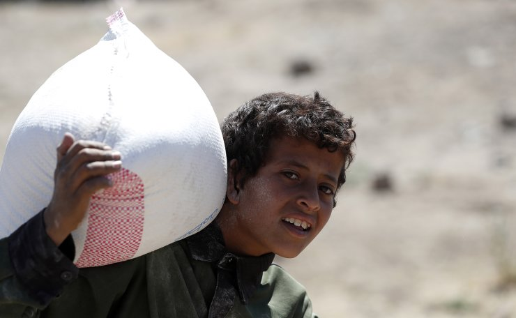 A conflict-affected Yemeni boy carries a sack of flour provided by Mona Relief Yemen, at an area on the outskirts of Sanaa, Yemen, 03 December 2019. According to reports, the International Rescue Committee (IRC) has warned that five more years of war in Yemen would cost some 29 billion USD in humanitarian aid, as ​the prolonged conflict in the Arab country has created the worst humanitarian crisis in the world, with 10 million people living with extreme hunger and​ two million children under five already acutely malnourished. EPA