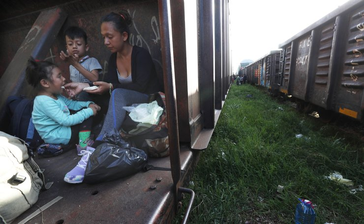 A migrant mother feeds her children in a freight train in Palenque, Chiapas state, Mexico, as they travel north on June 24, 2019. AP