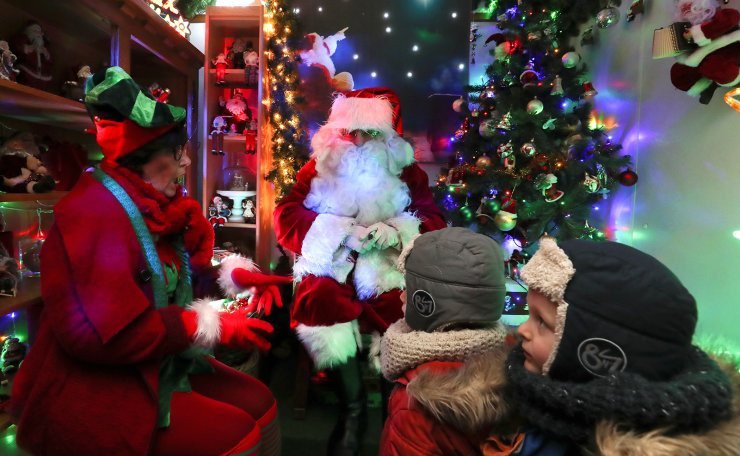 A man dressed as Santa Claus (Father Christmas) interacts with children in a house that belongs to Serge Hennebel, nicknamed 'Elf Serge' and has been transformed into a Christmas village adorned with hundreds of lights, in Hamme-Mille, Belgium December 7, 2019 . Reuters
