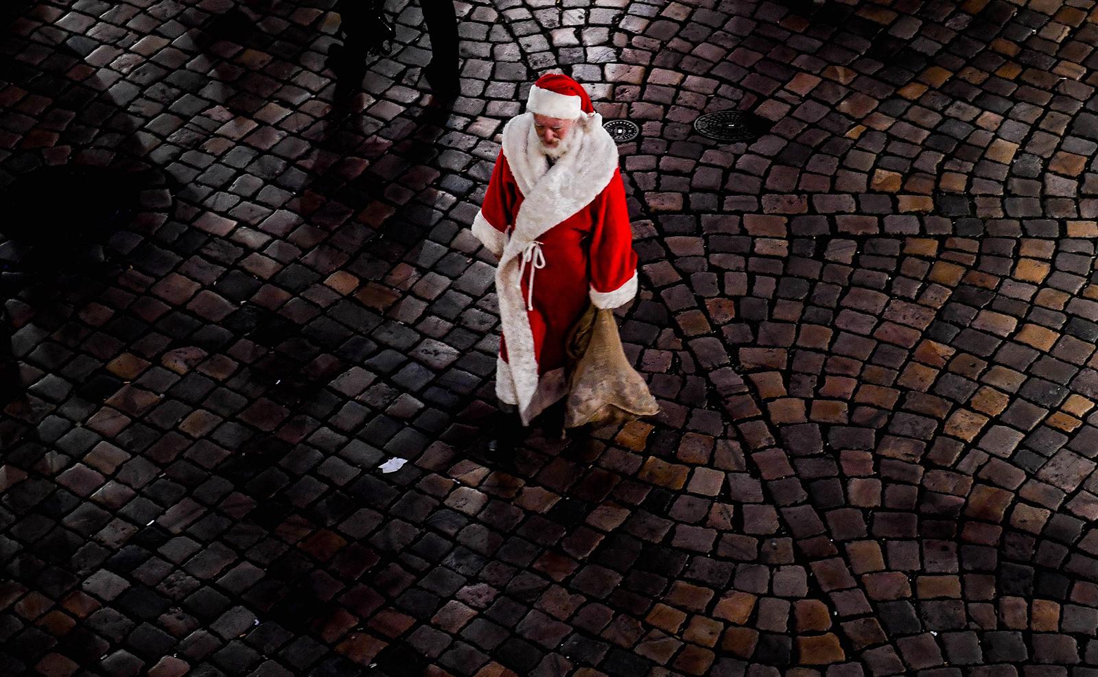 A man dressed as Santa Claus walks near a Christmas market in Dresden, Germany, 11 December 2019. EPA
