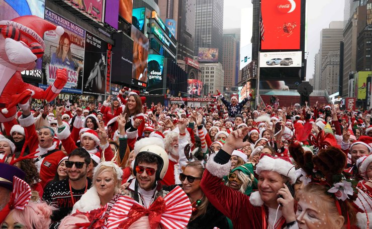 Revellers gather for the start of the Annual SantaCon Bar Crawl at Father Duffy Square, a section of Times Square, on December 14, 2019, in New York. - SantCon is an event where people make donations to charitable causes and dress up as a Christmas character and visit bars around the city. AFP