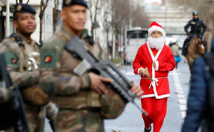 A runner dressed as Santa Claus walks past soldiers before the start of the Christmas Corrida Race in Issy-les-Moulineaux, near Paris, France, December 15, 2019. Reuters