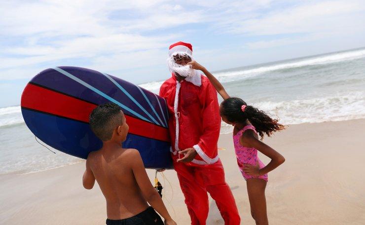 Carlos Bahia, dressed as Santa Claus, greets children at the Maresias beach in Sao Sebastiao, hometown of WSL World Champion Gabriel Medina, Sao Paulo state, Brazil December 15, 2019. Reuters