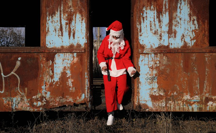 A charity worker wearing a Santa Claus costume jumps out of an abandoned train carriage after delivering Christmas presents to a poor family on the outskirts of Brasov, Romania, Sunday, Dec. 15, 2019. AP