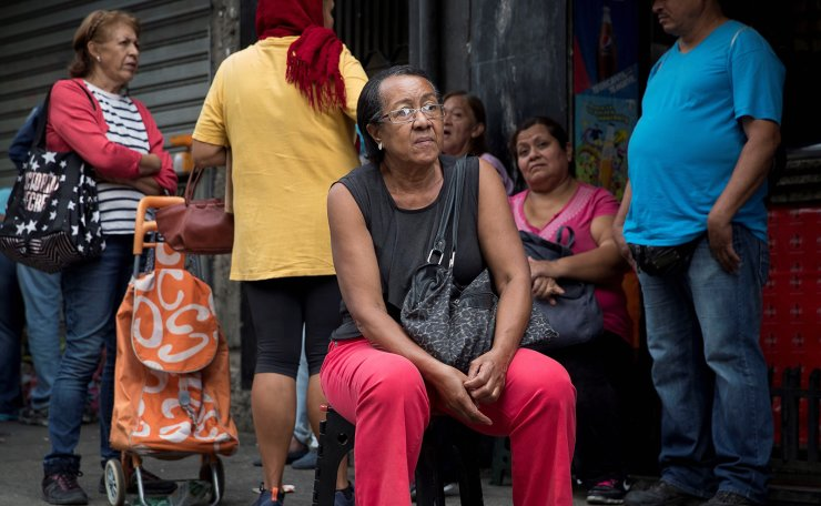 Pensioner Antonieta Adames waits in front of a supermarket that accepts payments in Petro tokens, in Caracas, Venezuela, 28 December 2019 (issued 29 December 2019). Millions of pensioners and public servants received petro token handouts by Venezuelan President Maduro as a Christmas bonus. The Petro is a cryptocurrency issued by the government of Venezuela.  EPA