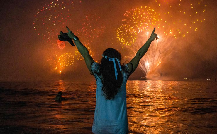 A woman celebrates as she watches the traditional New Year's fireworks at Copacabana Beach in Rio de Janeiro, Brazil, on December 31, 2019. AFP