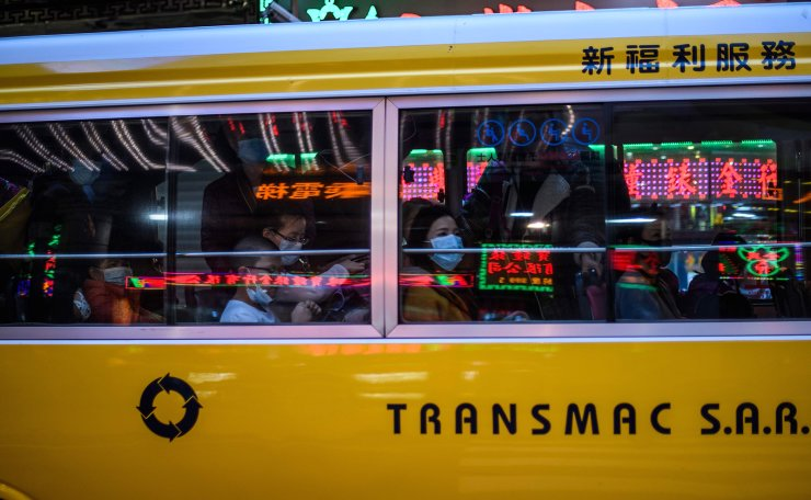 Commuters wear face masks as they travel in a bus in Macau on January 22, 2020, after the former Portuguese colony reported its first case of the new SARS-like virus that originated from Wuhan in China. AFP