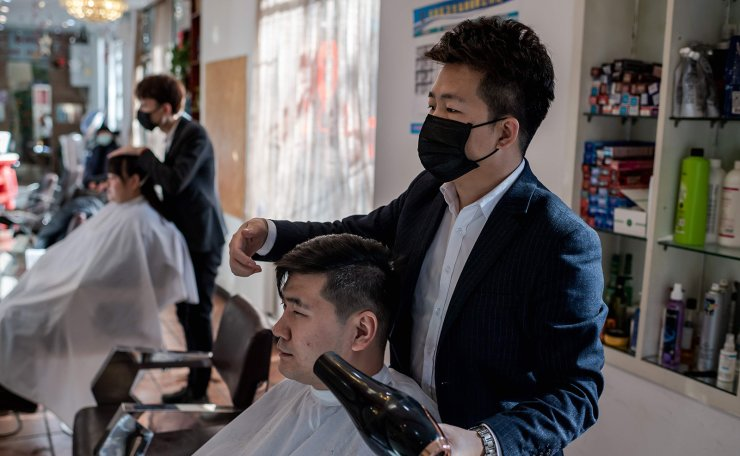 Hairdressers wear protective masks as they cut the hair of customers in Beijing on January 23, 2020. AFP