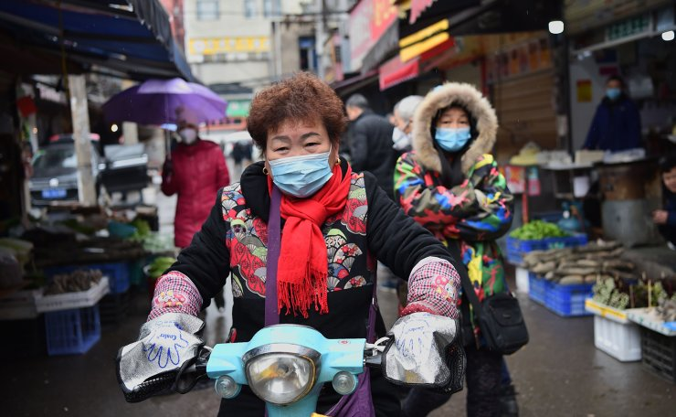 A woman wearing a facemask to help stop the spread of a deadly virus which began in the city rides her scooter through a market in Wuhan on January 24, 2020. AFP