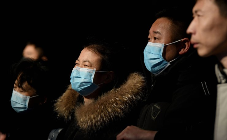 Passengers wearing protective facemasks to help stop the spread of a deadly SARS-like virus which originated in the central city of Wuhan arrive at Beijing railway station in Beijing on January 24, 2020. AFP