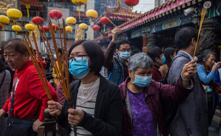 People wear masks as they visit Wong Tai Sin temple on the first day of the Lunar New Year of the Rat in Hong Kong on January 25, 2020, as a preventative measure following a coronavirus outbreak which began in the Chinese city of Wuhan. AFP