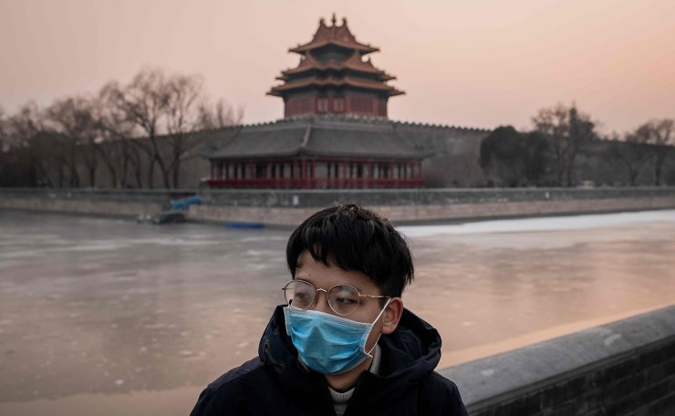 This picture taken on January 25, 2020 shows a man wearing a protective facemask to help stop the spread of a deadly SARS-like virus which originated in the central city of Wuhan outside the Forbidden City (in background) in Beijing. AFP
