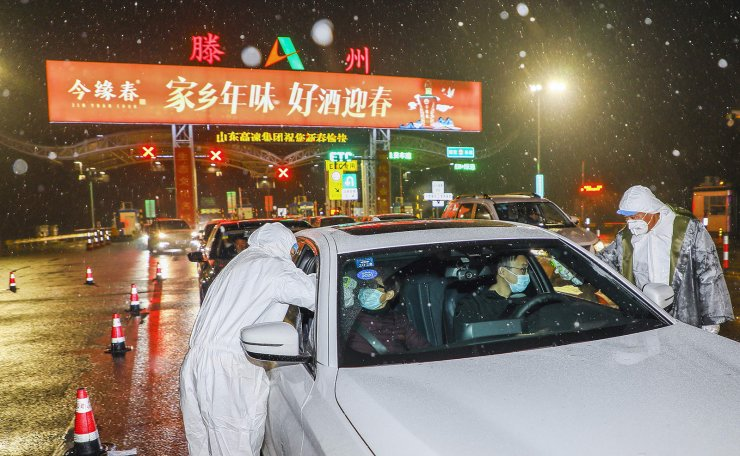 This photo taken on January 26, 2020 shows medical staff members wearing protective clothing to help stop the spread of a deadly virus which began in Wuhan, checking the temperature of drivers and passengers at a highway check point in Tengzhou in China's eastern Shandong province. AFP