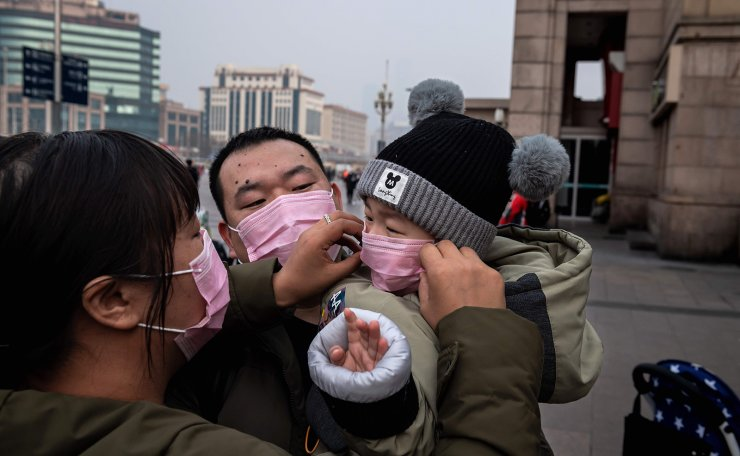 A mother (L) of a child (R) held by his father (C) adjust his protective mask to help stop the spread of a deadly virus which began in Wuhan peaks through a plastic curtain at the Beijing railway station in Beijing on January 27, 2020. AFP