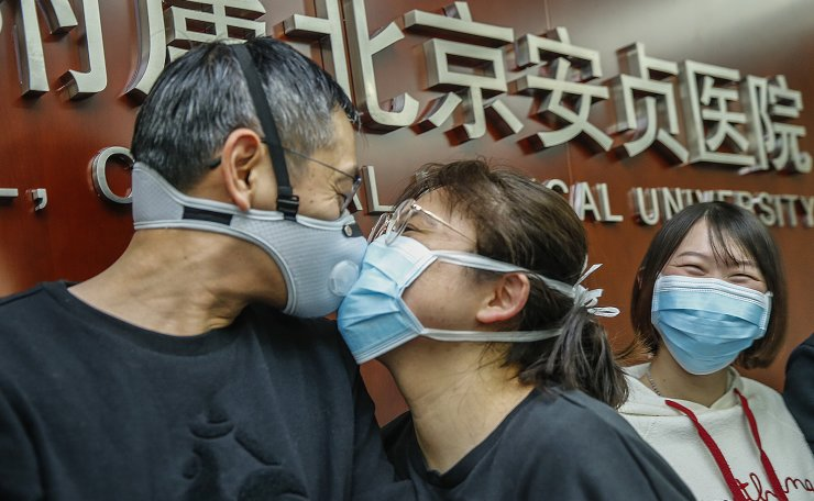 Cao Liyao (C), a member of a medical team, kisses goodbye to her husband Wang Bin before leaving for Wuhan of Hubei Province, in Beijing, capital of China, Jan. 27, 2020. A team comprised of 136 medical workers from Beijing left for Wuhan City on Monday to aid the novel coronavirus control efforts there. Xinhua