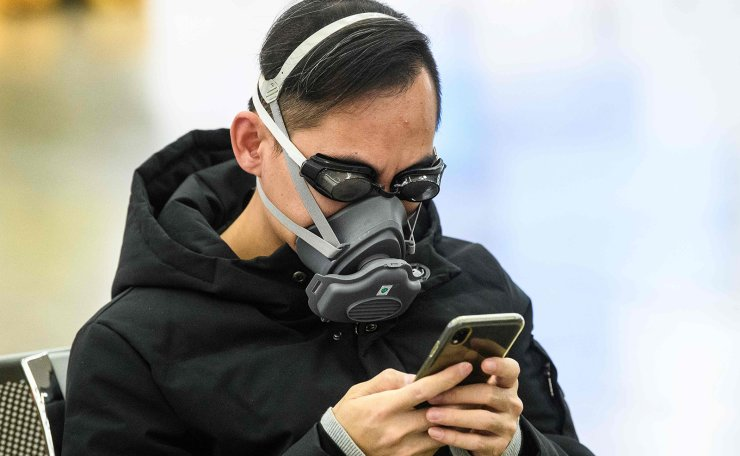 A passenger wears swimming goggles and a facemask as he waits inside the high-speed train station connecting Hong Kong to mainland China during a public holiday in celebration of the Lunar New Year in Hong Kong on January 28, 2020, as a preventative measure following a virus outbreak which began in the Chinese city of Wuhan. AFP