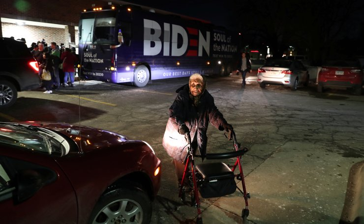 An elderly woman pushes a walking frame past a bus belonging to Democratic 2020 U.S. presidential candidate and former Vice President Joe Biden's campaign in Des Moines, Iowa, U.S., February 2, 2020. Reuters