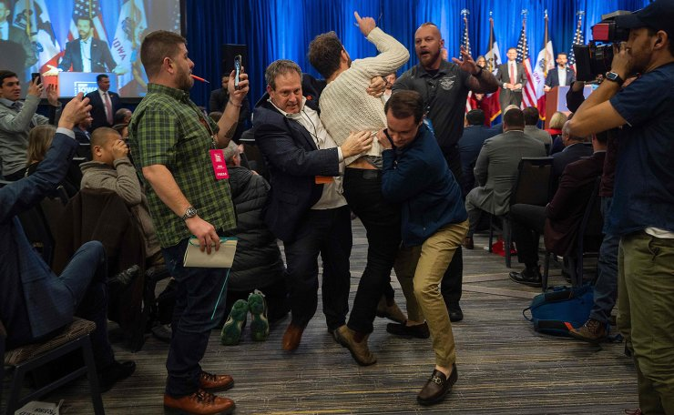 A protester is dragged from the room as Donald Trump Jr. (Top R) speaks with his brother Eric during a 'Keep Iowa Great' press conference in Des Moines, IA, on February 3, 2020. AFP