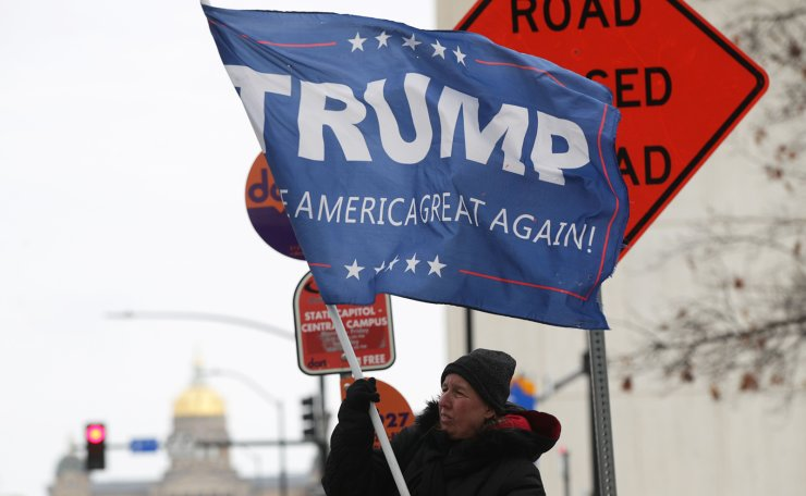 A woman holds a Trump flag on the street February 3, 2020 in Des Moines, Iowa. Iowans will pick their choices for Democratic presidential candidate at the state caucuses this evening, the first in the primary season. AFP