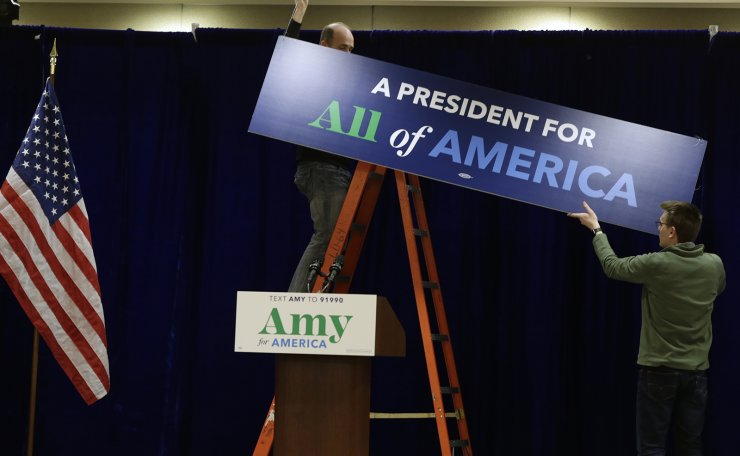 Staff members hang a sign before a caucus night party for Democratic presidential candidate Sen. Amy Klobuchar, D-Minn., in Des Moines, Iowa, Monday, Feb. 3, 2020. AP