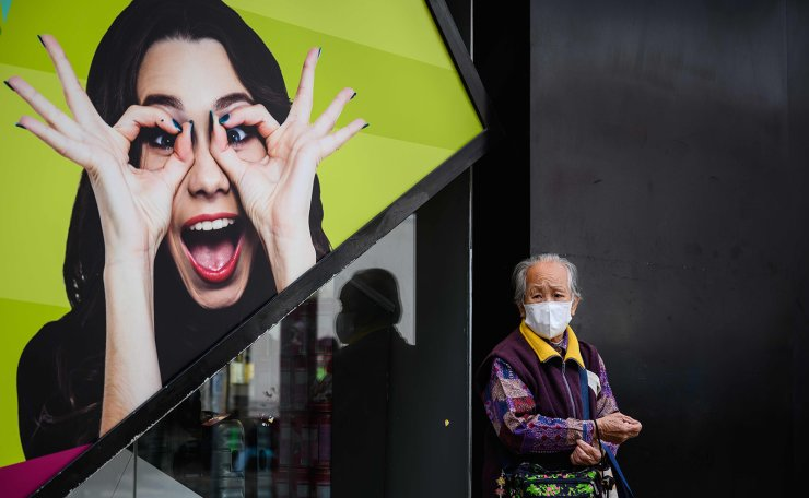 This photo taken on February 6, 2020, shows an elderly lady wearing a face mask as a preventative measure following a coronavirus outbreak which began in the Chinese city of Wuhan, as she stands outside a shop in the Sheung Shui area of Hong Kong, near the Chinese border. AFP