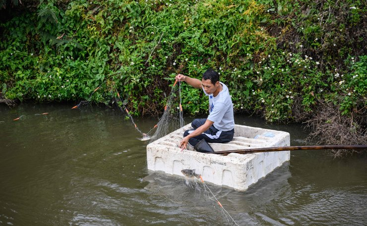This photo taken on February 6, 2020, shows a man fishing on a makeshift polystyrene raft in Ma Tso Lung in Hong Kong, near the border with the Chinese mainland city of Shenzhen. AFP