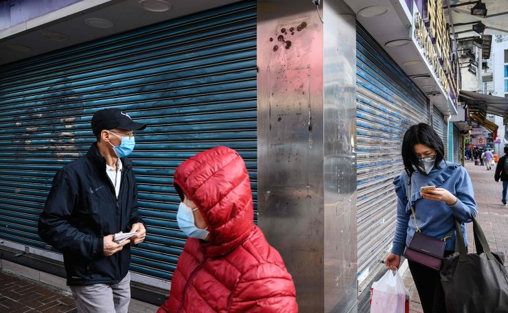 This photo taken on February 6, 2020, shows pedestrians wearing face masks as a preventative measure following a coronavirus outbreak which began in the Chinese city of Wuhan, as they walk past a shuttered shop in the Sheung Shui area of Hong Kong, near the Chinese border. AFP
