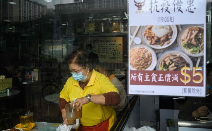 This photo taken on February 6, 2020, shows a waitress wearing a face mask as a preventative measure following a coronavirus outbreak which began in the Chinese city of Wuhan, as she cleans a table in a restaurant that has a notice offering an anti-epidemic discount which starts at 7pm each day, with all main menu items discounted by 5 HKD, in the Sheung Shui area of Hong Kong, near the Chinese border. AFP