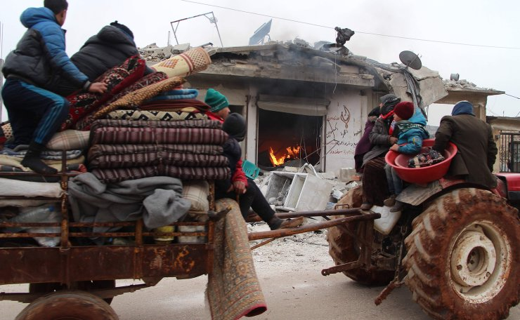 Displaced Syrians pass a house still on fire as they flee shelling on the town of Abyan, in the western rebel-held part of the northern Syrian province of Aleppo, near the border with Turkey, on February 13, 2020. - The regime of Syrian President Bashar al-Assad has made major inroads in the last opposition-held area in the northwest of Syria since December, sending 700,000 people fleeing their homes in the provinces of Idlib and Aleppo towards the closed Turkish border in harsh winter conditions. AFP