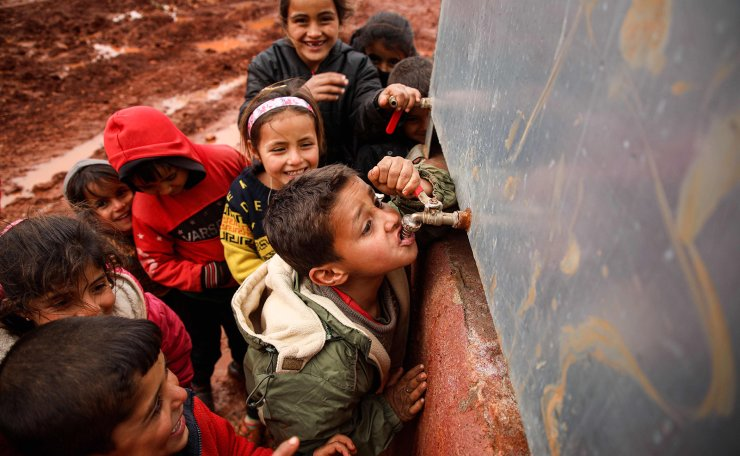 A child drinks from the tap of a cistern as others queue behind him at a flooded camp for displaced Syrians near the village of Killi in the north of the northwestern Idlib province on February 8, 2020. AFP