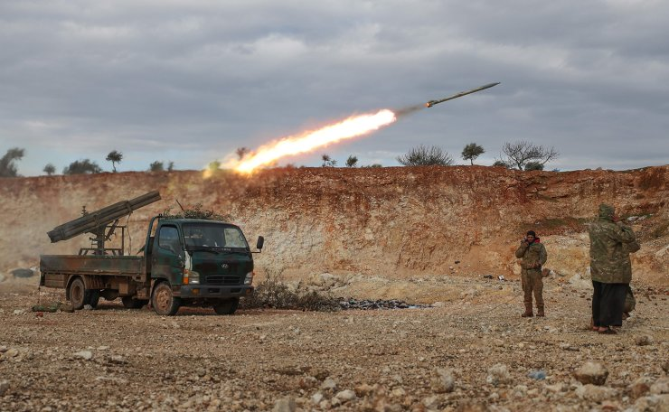 Syrian rebel fighters fire a Grad rocket towards government forces in northwestern Syria on February 8, 2020. - Since December, government forces have pressed a blistering assault against the Idlib region with Russian support, retaking town after town despite warnings from rebel ally Turkey to back off. AFP