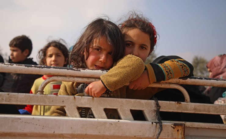 Displaced Syrian girls stand in the back of a truck parked at a newly-established camp on the edges of Maaret Misrin town in Syria's Idlib province, on February 6, 2020. AFP