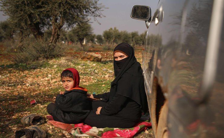 Displaced Ghossoon sit with her child on a blanket on the outskirts of Maaret Misrin town in Syria's Idlib province on February 6, 2020, after fleeing regime and Russian bombardment. AFP