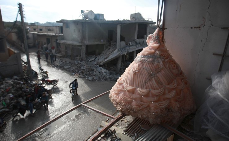 A wedding dress is seen in the destroyed window of a bridal shop in a damaged building in Balyun in Syria's northwestern Idlib province, on December 8, 2019, the day after a reported Russian airstrike on a market in the village. AFP