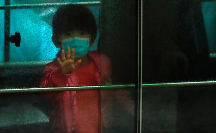 A child waves as she sits in a vehicle carrying residents evacuated from a public housing building, following the outbreak of the novel coronavirus, outside Hong Mei House, at Cheung Hong Estate in Hong Kong, China February 11, 2020. Reuters