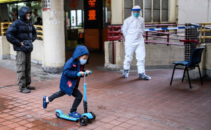 A child wearing a face mask rides his scooter past a police officer (R) wearing protective gear outside Hong Mei House at Cheung Hong Estate in Hong Kong on February 11, 2020, following the evacuation of more than 100 people from the housing block after four residents in two different apartments tested positive for the new coronavirus. - Officials said the relocation of residents in Tsing Yi district was a precautionary measure after three members of the same family contracted the virus. AFP