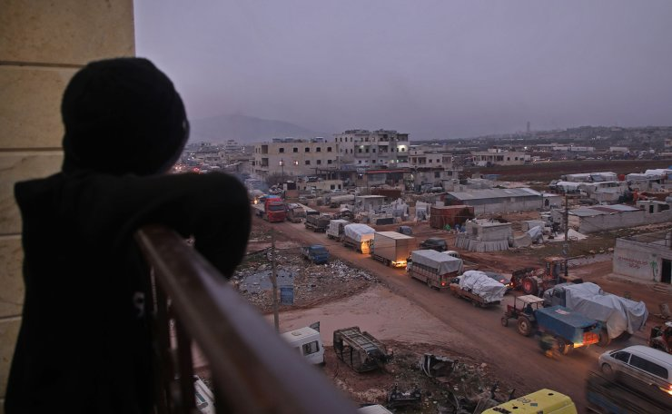 A child in the Syrian town of Dana, east of the Turkish-Syrian border in the northwestern Syrian Idlib province, watches from a balcony as a large convoy of displaced people who fled pro-regime attacks on rebel-held areas of the same province seek shelter in safer parts, on February 11, 2020. AFP