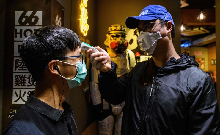 In this photo taken on February 11, 2020, Sam Wong (R), who owns 66 Hotpot, a family-run restaurant in the bustling district of Mongkok, takes the temperature of a member of staff outside his restaurant in Hong Kong. AFP