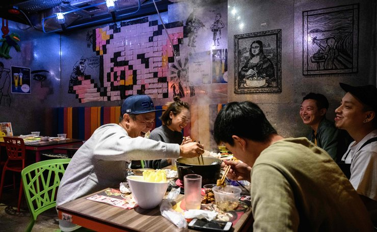 In this photo taken on February 11, 2020, a group of friends share a laugh as they eat together at 66 Hotpot, a family-run restaurant in the bustling district of Mongkok in Hong Kong. AFP