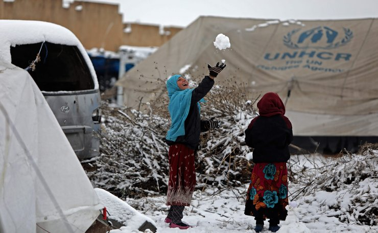 Children who fled pro-regime forces attacks in northeastern Syria, play in the snow at a camp for displaced people in the northern Syrian town of Tal Abyad by the border with Turkey, on February 13, 2020. - A wave of displacement that has seen around 700,000 people flee a regime offensive in Syria's Idlib region is the biggest of the nine-year-old conflict, the United Nations said. AFP