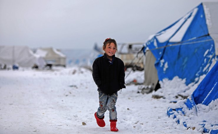 A child who fled pro-regime forces attacks in northeastern Syria, is pictured in front of tents at camp for displaced people in the northern Syrian town of Tal Abyad by the border with Turkey, on February 13, 2020. AFP