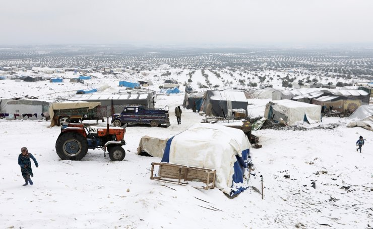 Internally displaced people walk on snow near tents at a makeshift camp in Azaz, Syria February 13, 2020. Reuters