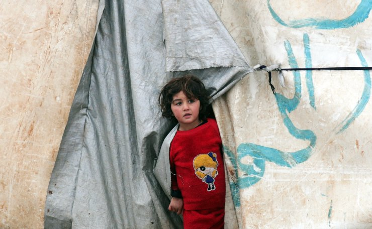 An internally displaced girl looks out from a tent in Azaz, Syria February 13, 2020. Reuters