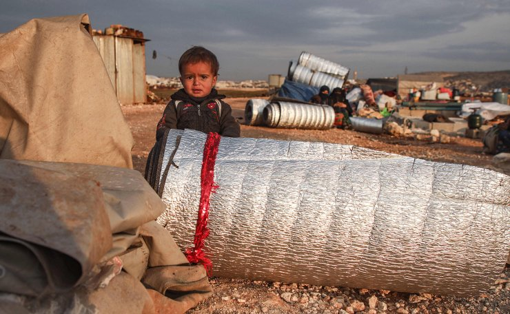 A child stands behind rolled-up thermal insulation foil out in the open at a camp for displaced Syrians east of Sarmada in the north of the northwestern Idlib province on February 16, 2020, as people prepare to flee the camp. AFP