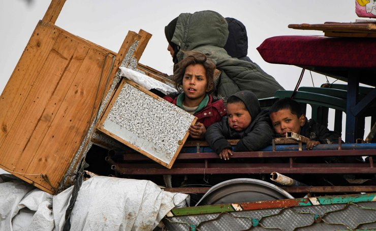 Children ride in the back of a truck with furniture, mattresses, and blankets while passing by an internally-displaced persons (IDP) camp by Dayr Ballut near the Turkish border in the west of Syria's northern province of Aleppo on February 16, 2020, fleeing advancing Syrian government forces in Idlib and Aleppo provinces. AFP