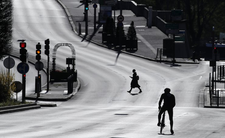A woman crosses an empty street in Suresnes, outside Paris, Monday, March 30, 2020 as the government announced an extension of the initial 15-day home confinement period that came into force on March 17 in a bid to brake the spread of the Covid-19. AP