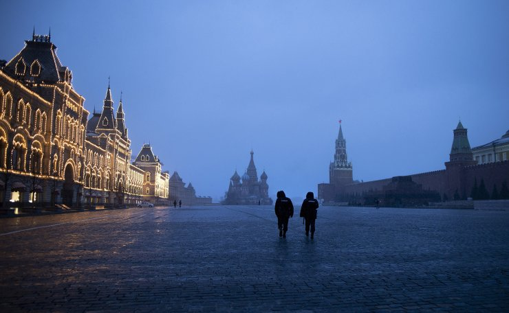 Two police officers patrol an almost empty Red Square, with St. Basil's Cathedral, center, and Spasskaya Tower and the Kremlin Wall, right, at the time when its usually very crowded in Moscow, Russia, Monday, March 30, 2020. Russian President Vladimir Putin says the country has managed to slow down the spread of coronavirus but should be prepared for contagions to quickly grow. The new coronavirus causes mild or moderate symptoms for most people, but for some, especially older adults and people with existing health problems, it can cause more severe illness or death.  AP