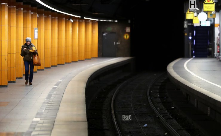 A woman walks along an empty platform downtown in Munich, Germany, Monday, March 30, 2020. In order to slow down the spread of the corona virus, the federal government has considerably restricted public life. The new coronavirus causes mild or moderate symptoms for most people, but for some, especially older adults and people with existing health problems, it can cause more severe illness or death. AP