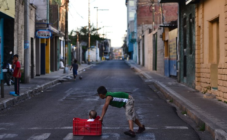 Children play in an empty street of Tegucigalpa on March 30, 2020 during the lockdown ordered by the Honduran government to help slow the spread of the COVID-19 coronavirus pandemic. AFP