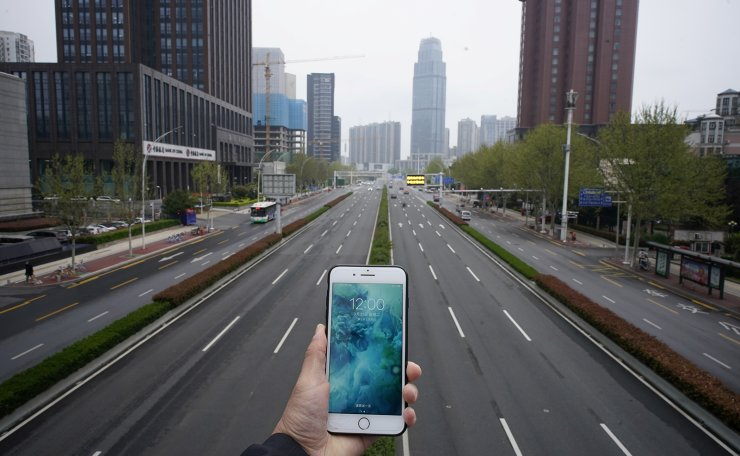 A mobile phone showing the time at noon, is displayed for a photo in front of an almost empty road with low traffic, during the coronavirus disease (COVID-19) outbreak, in Wuhan, Hubei province, China, March 31, 2020. Reuters